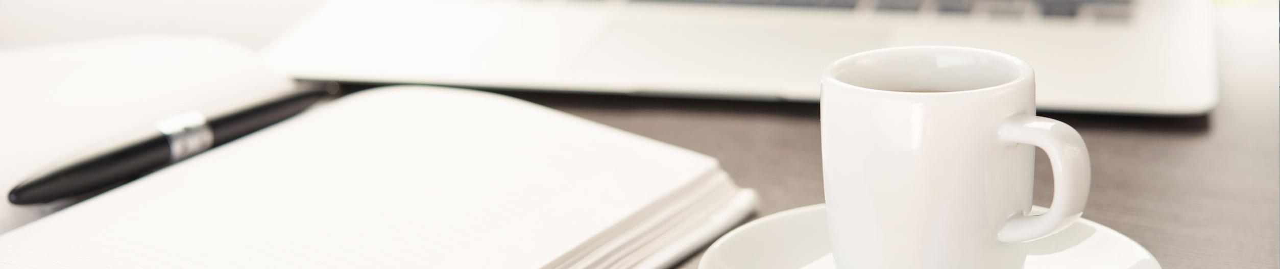 webagentur-mw-kontakt - das Bild zeigt einen modernen Arbeitsplatz mit einer Tasse Kaffee, einem Notizbuch und einem Laptop