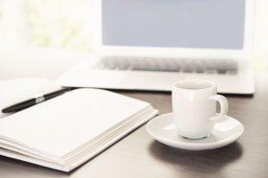 webagentur-mw - das bild zeigt einen stimmungsvoll arrangierten arbeitsplatz mit laptop, tasse und geöffnetem notizbuch