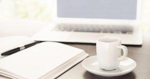 webagentur-mw-schwaebisch-hall - das bild zeigt einen modernen Arbeitsplatz mit geöffnetem Laptop, Notitzbuch und einer Tasse Kaffee