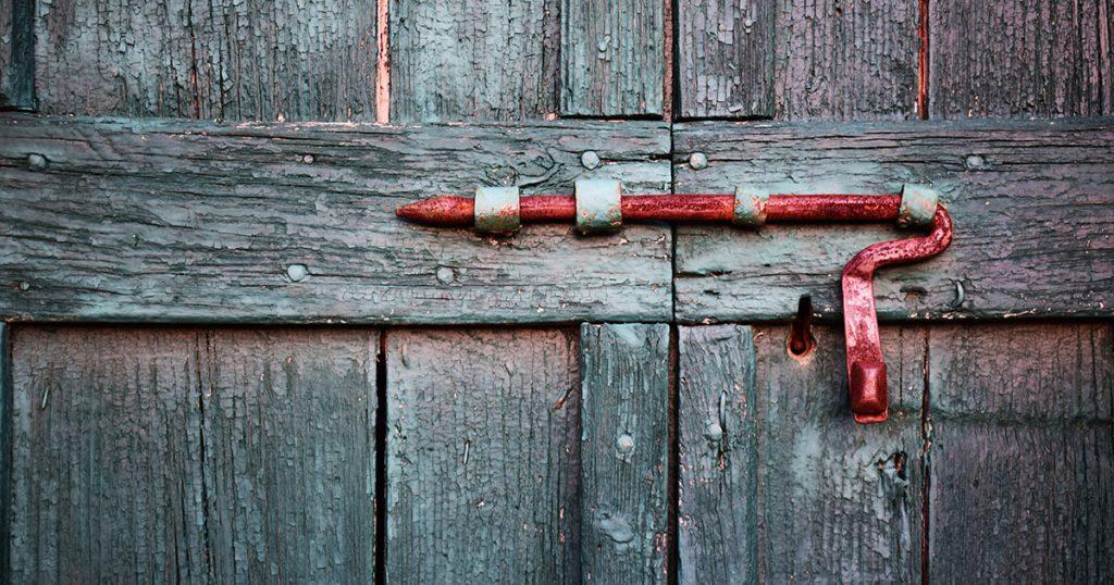 webagentur-mw-schwaebisch-hall - das bild zeigt ein altes Holztor, das von einem roten Metallhaken geschlossen gehalten wird.