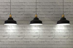 webagentur-mw - das bild zeigt 3 leuchtende hängelampen vor einer steinwand