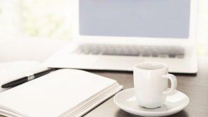 webagentur-mw - das bild zeigt ein weißes laptop und eine kaffeetasse auf einem schreibtisch mit einem aufgeschlagenem notizbuch