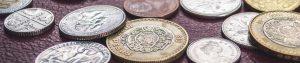 webagentur-mw - das bild zeigt verschiedene internationale münzen die auf einem tisch liegen