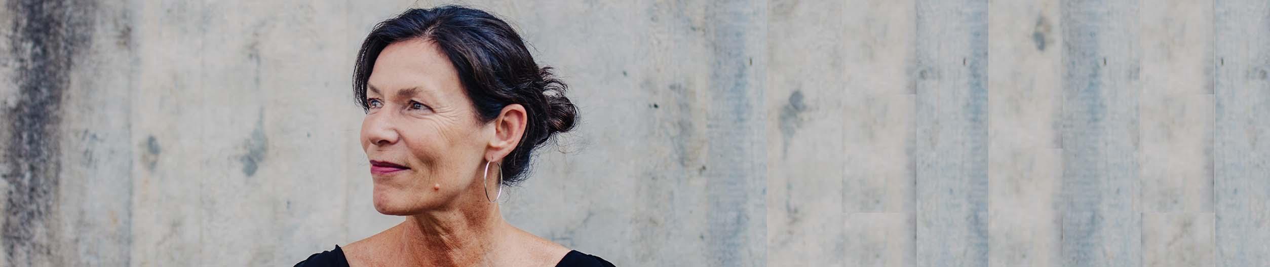 webagentur-mw - hier sieht man eine Portraitaufnahme von monica wenczel vor einer betonwand