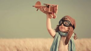 webagentur-mw - das bild zeigt einen kleinen jungen mit fliegermütze und fliegerbrille der ein holzflugzeug in die luft hält